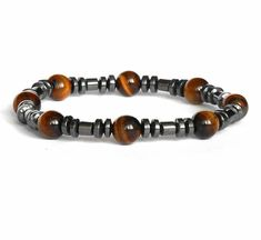 This mens gemstone jewelry is designed with shiny Hematite Beads and Tiger Eye - 8 mm ,gemstone strung on a durable stretch cord to adjust to your wrist size . Shiny Hematite discs and round used to separate the gemstones in this Mens bracelet . This brown on Tiger eye beads