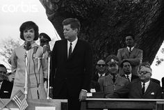 12/16/1961-La Morita, Venezuela: A speech in Spanish by Mrs. John F. Kennedy took La Morita's shirtsleeved peasants by storm today. She received the loudest cheers of President Kennedy's visit to Venezuela so far and her speech was televised and broadcast nationally. Mrs. Kennedy, who had been sitting beside President Romulo-Betancourt of Venezuela, approached the microphone and spoke unhesitatingly in perfect Spanish. She is shown here at the microphone with her husband beside her. Decem...