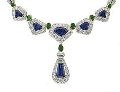 [DETAIL] A SAPPHIRE, EMERALD AND DIAMOND SUITE, BY CARTIER   The necklace designed as five pentagonal sapphire and diamond clusters with drop-shaped emerald spacers to the diamond backchain, suspending a sapphire and diamond drop-shaped pendant, with bracelet and ear pendants en suite, necklace 37.0 cm, bracelet 17.0 cm, ear pendants 3.5 cm long  Signed Cartier, Nos. R3068, R3070 and R3069