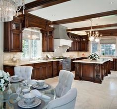 LOVE this kitchen!  Those chairs and he beams and the lights and the range hood, etc!  Yum!