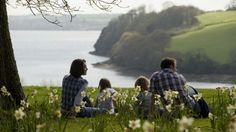 A family sit among daffodils with a view out to water beyond them