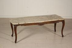 Tavolino da salotto in stile dalla linea mossa e intagliata. Piano sagomato in marmo.