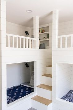 White shiplap bunk beds are located on adjacent walls on either side of a two tone staircase and are dressed in blue bedding. Bunk Bed Wall, Bunk Bed Rooms, White Bunk Beds, Bunk Beds Built In, Bunk Bed Lights, White Shiplap Wall, Modern Farmhouse Plans, Farmhouse Chic, Bunk Bed Designs