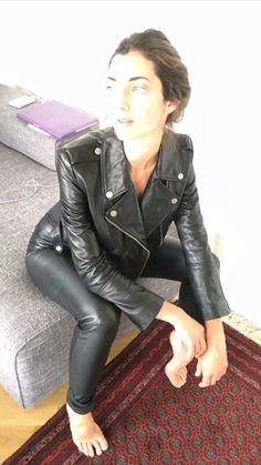 Barefoot amateur in bed in leather pants and leather moto jacket