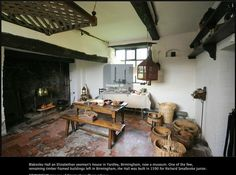 Blakesley Hall, Kitchen: View of the entire kitchen including the rear door to the kitchen garden, hanging cage allowed food to be stored safe from vermin but with a free flow of air, drying herbs or hung cured and freshly hunted game.