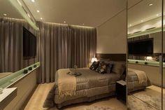 Painel da tv com espelho e prancha com penteadeira, cortina como substituta para a porta do closet.