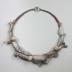 Archaeological objects. Necklace by Amanda & Matt Caines. Etched antique clay pipe parts recovered from the Thames river, fabric, wooden beads & stitchwork.