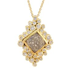 CUST-N-CUBE-FOXS:The custom made one of a kind pendant features a large raw cubed diamond, bordered by round brilliant cut diamonds each bezel set in 18K yellow gold in a cluster style design Diamond: