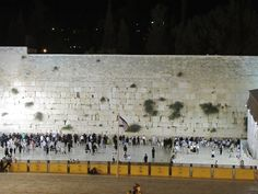 A typical midnight in June at the Western Wall Prayer Plaza. Wilson's Arch is to the left and the ramp for non-Muslim entrance to the Temple Mount through the Morocco Gate is to the right. The men's section is the larger portion to the left and the women's prayer section can be seen to the right next to the ramp. There is a thin five foot wall called a mehitza separating the men's and women's sections.