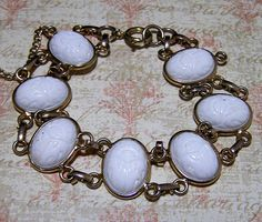 Mid Century milk glass scarab bracelet White molded glass scarabs are set sideways Unsigned Gold tone setting, spring ring clasp, safety chain 7 1/2 x 3/4 inch Oval stones are 13 x 17 mm Very good vintage condition, shows no signs of wear International buyers welcome, over charges are automatically refunded Priority shipping is optional 91717 Credit cards and Paypal are accepted.  Want to see more bracelets? Check out my other listings https://www.etsy.com/your/s...