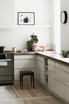 Witte, greeploze keuken. Houten werkblad. Oude, houten vloer.