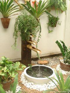 Fonte de água com bambu e viga de madeira.