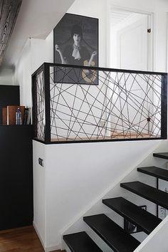Juste à côté des escaliers, un garde corps en fer noir hyper design trouve parfaitement sa place dans cette déco intérieure moderne dominée par le blanc et le noir