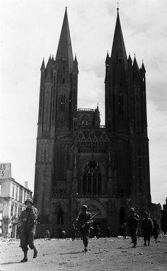 Une unité de la 1ère division d'infanterie américaine progresse devant la cathédrale de Coutances relativement épargnée par les bombardements. Photo prise vers le 29 juillet 1944. © US Army
