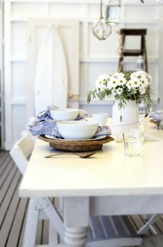 Gorgeous tablescape idea for a summer home or just a home looking to bring in summer! Can't go wrong with white-- it really makes the blue pop and the yellow of the daisies. Gorgeous!