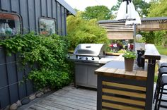 Compact outdoor kitchen features hardwood countertops, barstool seating, and large stainless steel grill, below a set of glass frame pendant lights.