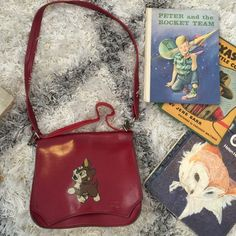 Vintage red dog purse, kids Vintage purse with adorable kid-like charm! Features a brown and white dog with a green(!!) tongue. The outside of the purse shows some age, but the inside is very clean. Has 2 straps- the long strap in good vintage condition and the shorter strap, which is bent, as shown in the photos. The original owner of the purse told me it came from Russia. **books not included** Vintage Bags