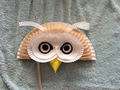 Tawny owl mask. Also made from half a paper plate and some cup cake or patty cake cases. The brown background feathers are from the top edge of baking paper liner for a loaf tin. The eyebrows are the cut rims or a cup cake case. No eye holes as it is to be held on a stick, but it would be simple enough to cut the holes out if desired.