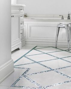 Iridescent aquamarine-colored glass mosaic crisscrosses a marble bathroom floor, staying within its own blue border to mimic an area rug. Designer: Interieurs Finnie Ward Shown: Sicis Iridium 5/8 by 5/8 in Hyacinth, $30 per sq. ft.; Artistic Tile and Stone