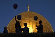 Palestinian children hold balloons during the Muslim holiday of Eid al-Adha, near the Dome of the Rock Mosque in the Al Aqsa Mosque compound in Jerusalem's old city. Muslims will slaughter cattle and goats later, with the beef and meat distributed to the needy in the holiday which honors the prophet Abraham for preparing to sacrifice his son on the order of God, who was testing his faith. (AP Photo/Mahmoud Illean)