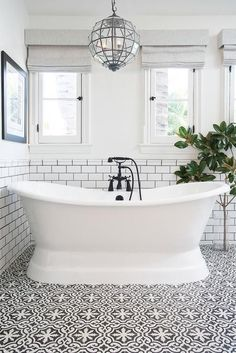 White and black bathroom features top half of walls painted white and bottom half of walls clad in white subway tiles finished with black grout lined with a glass faceted lantern hanging over a roll top bathtub fitted with an oil rubbed bronze tub filler placed atop a white and black Cement Tile Shop Bordeaux Tiles.