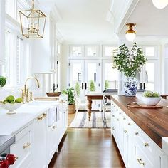 Beautiful traditional white kitchen with butcher block counters and brass details.