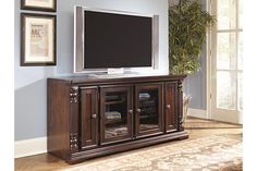 Dark brown TV stand with glass door storage area below and side storage doors