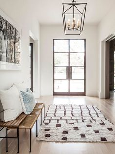 Glass and steel double front doors lead to a beautifully designed foyer featuring a Darlana Medium Lantern. Glass and steel front doors are by Lincoln Windows. #Glassandsteel #frontdoor #Glassandsteelfrontdoor Coats Homes