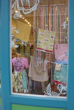 Teeny store window with great display! http://TGtbT.com says what makes this special are the white painted swirls around the edges and the ribbon curtain  backdrop! More Window Display Ideas for Resale & Consignment in the TGtbT.com Products for the Professional Resaler