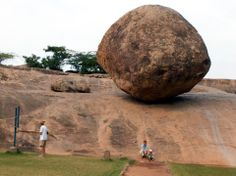 Krishna's Butterball, Mamallapuram, India ---- On the other side of the Mahabalipuram beach, is a particular rock that catches your eye. It's a popular tourist spot for picture taking, but for the local kids the hillside is a great natural slide. Legend has it that the Pallava rulers attempted to move the boulder with help of elephants, but to no avail. A brief distance from the Butterball is the Ganesha Mandapam, a temple etched out of a single rock.