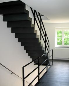 Moderne stalen trap op maat met zwarte balustrade.