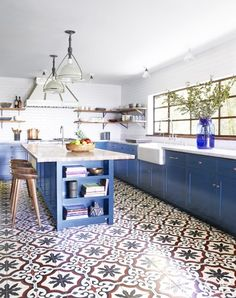 We love the bold colbalt blue cabinets, copper stool mosaic tiles, and vintage pendants—everything, basically. This kitchen is perfect.