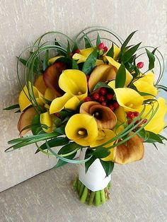 Several shades of yellow calla lilies are combined with cherry red hypericum berries in this bouquet. Grass leaves are looped around the perimeter and mimic the shapes of the calla lilies.