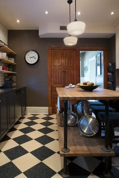 Cronin built the kitchen island out of butcher block and pipe. He added hooks underneath to hang the pots and pans.  Eclectic Kitchen by Margot Hartford Photography