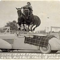 cowgirl tricking two horses over a vintage car