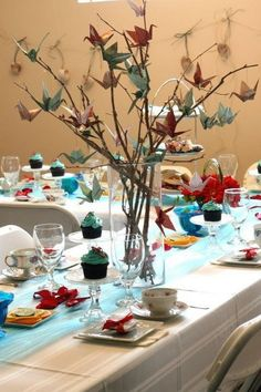 origami paper cranes hanging from twigs centerpieces 、 http://www.himisspuff.com/origami-wedding-ideas/6/