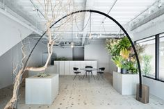 The arch, which rests on a pair of wooden trunks | Gigi Verde flower shop by Sides Core