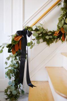 christmas garland swag on staircase with pine cedar magnolia silver dollar eucalyptus and black satin ribbon