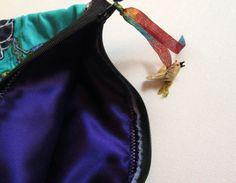 handmade, zipper Bag use as a purse, make up bag, etc.  materials: vintage fabric, thread, buttons, metal tag, glass bird, ribbon, zipper and a lot of imagination. photo 2/4