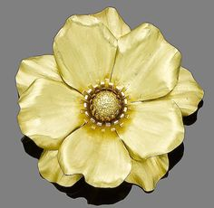 A gold flower brooch, by Cartier, 1955  Realistically modelled as a flowerhead with 18 carat gold petals and stamen, signed Cartier London, numbered, London hallmark, maker's mark, length 6.0cm, maker's case