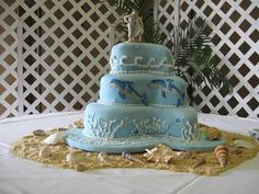 Dolphin Wedding Cake - Paisley cake pans.  White cake with passion fruit filling covered in fondant.  Dolphins are fondant and all other decorations buttercream.  Sand is made from crushed vanilla wafers.