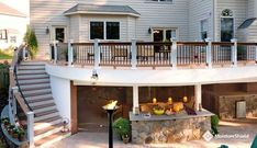 Walk out composite deck with curved stairs and wet bar below