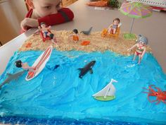 Beach cake,  Super easy for anyone!  just crush vanilla wafers or graham crackers and sprinkle on for sand, then frost waves and water in blue.  We used the Playmobil beach set and some party store accessories.