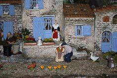 Une dame assise sur un banc chuchote à l'oreille de son mari (santons Gasquet).
