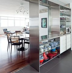 De aparência moderna, o aço inoxidável foi explorado no projeto do escritório AMZ Arquitetos. O material é marcante na divisão entre a cozinha e a sala de jantar. O maior nicho vazado é o passa-prato. Nos outros, são dispostos louças e taças