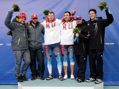 Sochi 2014 Day 11 - Bobsleigh Two-man Heat Silver medalists Beat Hefti and Alex Baumann of Switzerland team 1, gold medalists Alexander Zubkov and Alexey Voevoda of Russia team 1 and bronze medalists Steven Holcomb and Steven Langton of the United States team 1 celebrate during the flower ceremony for the Men's Two-Man Bobsleigh on Day 11 of the Sochi 2014 Winter Olympics at Sliding Center Sanki