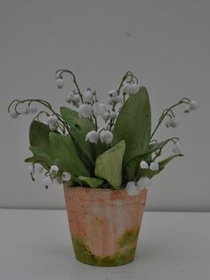 "Lily of the Valley.  Porcelain Flowers, Leaves, and Pot.  Tole Stems.  Approx.  8""."