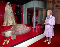 Queen Elizabeth II is pictured in 2007 looking at her 1947 wedding gown and bridal trail designed by Norman Hartnell with the naval uniform worn by the Duke of Edinburgh