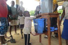 Boy washing his hands using handwashing equipment provided by Plan.