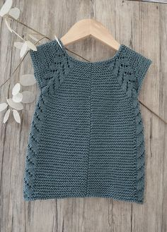 This seamless little top down dress / tunic top is an easy knit, worked in garter stitch with a simple leaf pattern forming the front borders, then cascading down the sides. I would rate this pattern suitable for the intermediate knitter. The pattern comes with schematics, and row by row instructions. Best of all…. No seaming !!.